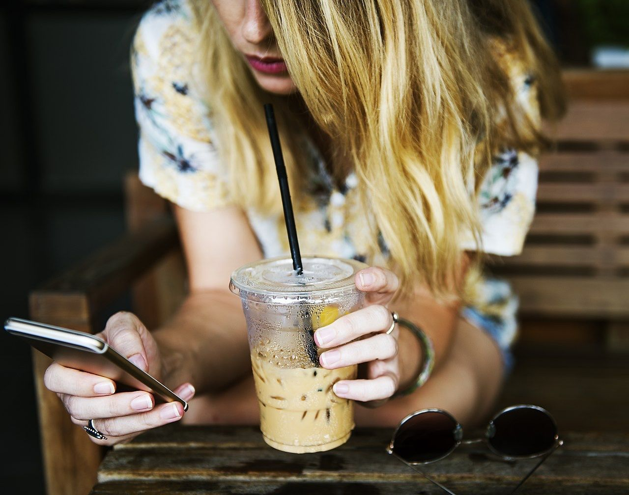 1280px-Texting_over_iced_coffee_(Unsplash)