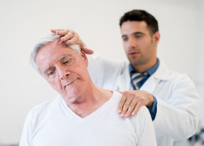 Chiropractor testing a patient with neck stiffness