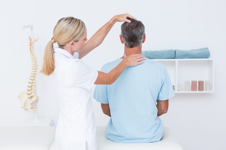 Chiropractor adjusting man's neck