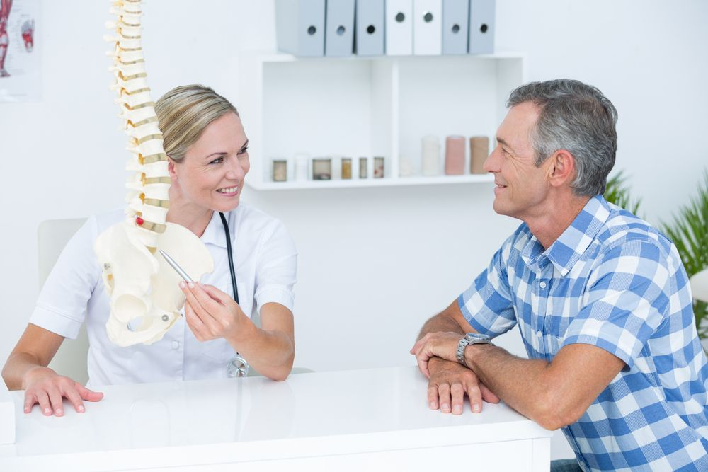 Chiropractor speaking with a patient
