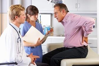 Chiropractor listening to a patient during their first visit