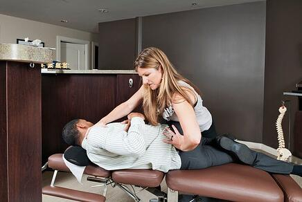 Chiropractor performing a side posture adjustment for low back pain